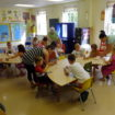 teachers assist children in Sunday school classroom