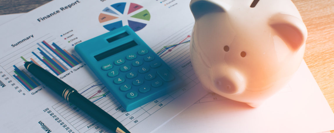 financial charts, calculator, and piggy bank