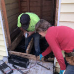 Barry Rae (left) and Betty Williams work together to remove rotted wood