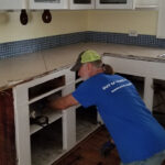 Don Williams removes cabinets in a water-damaged kitchen