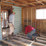 Don Williams (left) and Barry Rae replace floor joists in a room
