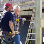 Dick Mahlmann (right) drills bolt holes with a local Ocracoke contractor for a wheelchair ramp the crew constructed